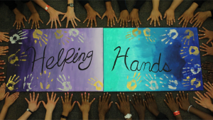 Student hands surround a poster that reads Helping Hands